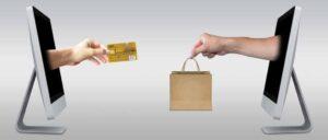 ידיים אנושיות יוצאות מ-2 מחשבים באחת סל קניות ובשנייה כרטיס אשראי