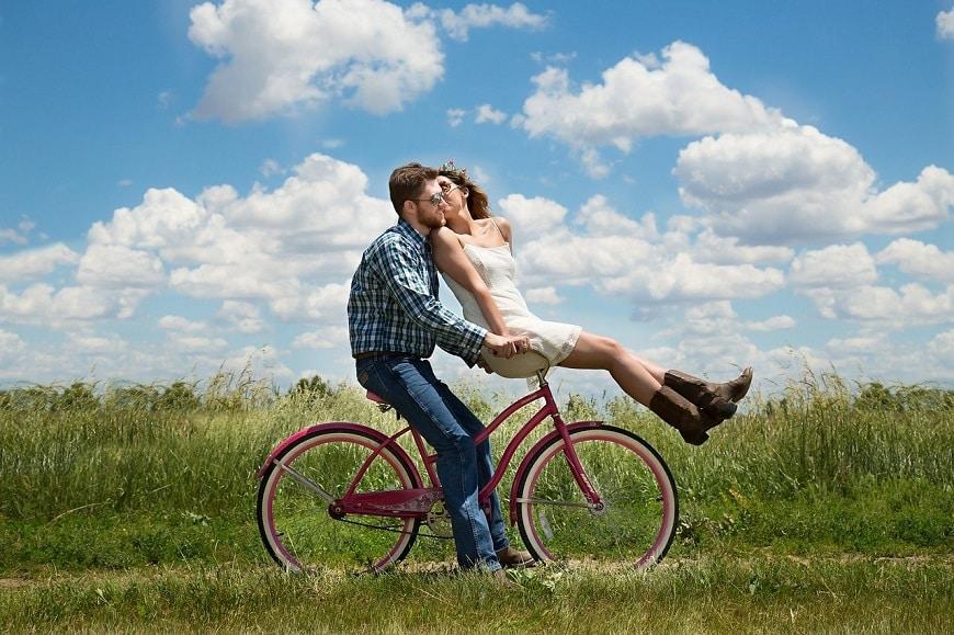 זוג מאוהב שהכיר באתר הכרויות רוכב יחד על אופניים