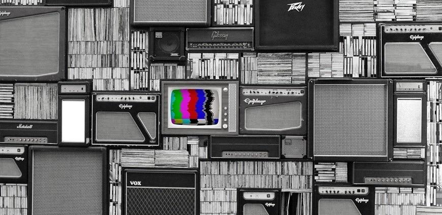 קיר עמוס פריטים שחור לבן עם מסך טלוויזיה צבעוני