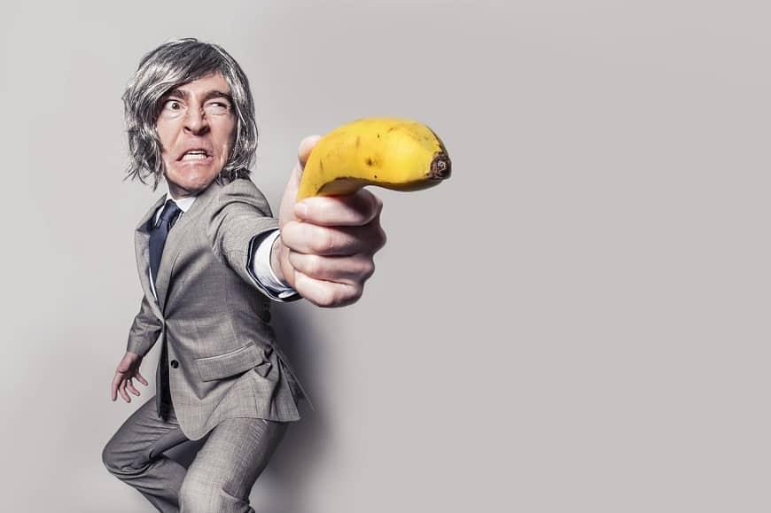 איש עם חליפה מכוון אקדח עשוי בננה